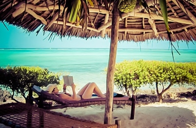 A woman reads next to the beach in Zanzibar